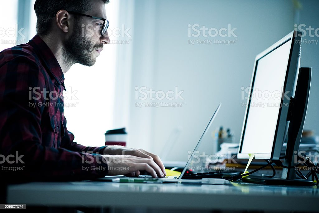 Young designer working on computer stock photo