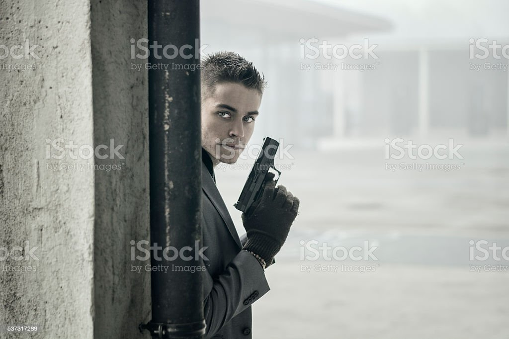 Young detective, policeman or mobster in an urban setting holding stock photo