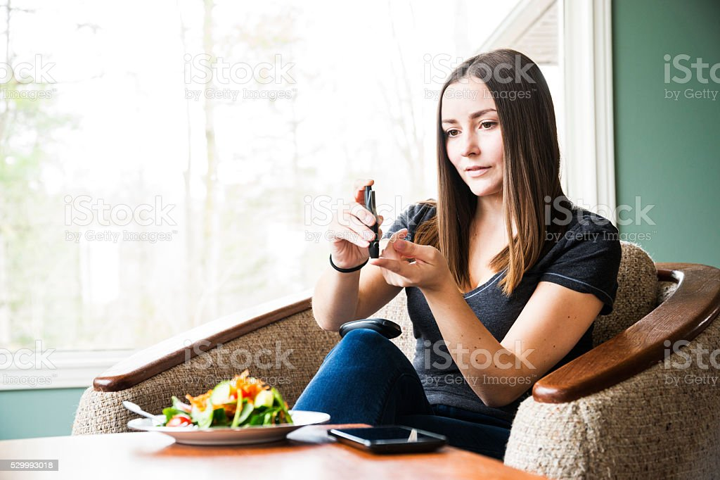 Young diabetic woman checking her blood sugar levels stock photo