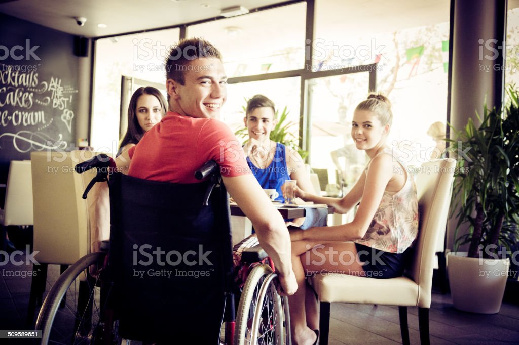 young disabled man having fun with his friends at cafe stock photo