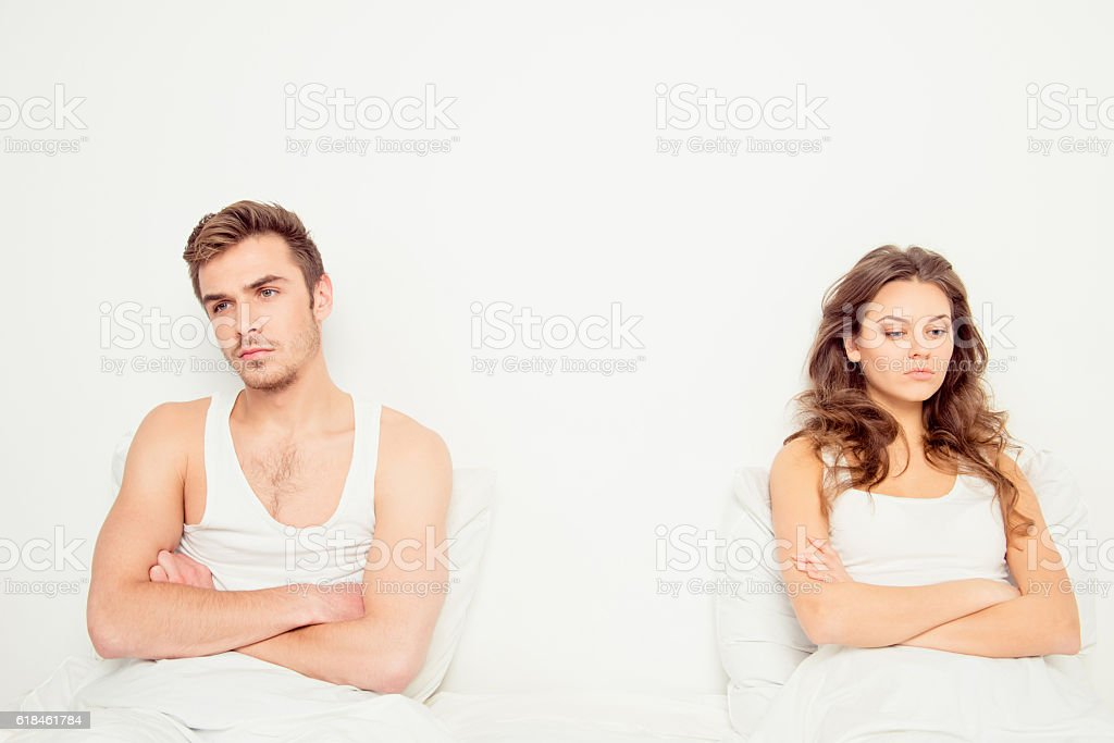 Young disconnected couple sitting on the bed stock photo