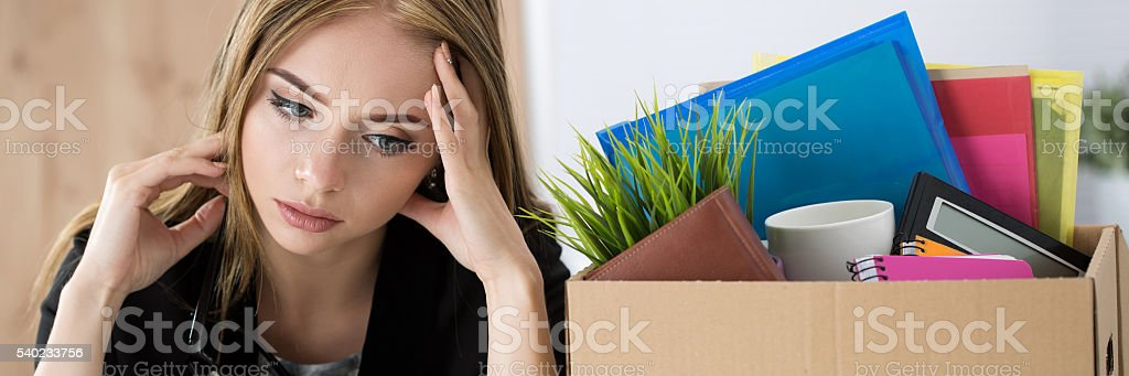 Young dismissed female worker sitting near the carton box stock photo