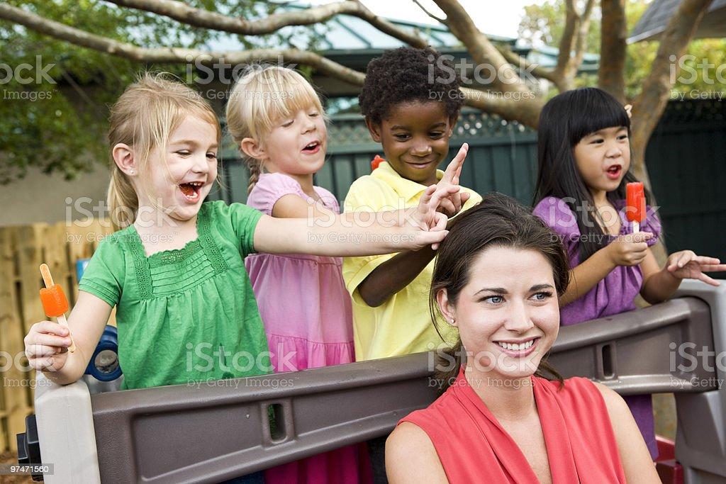 Young diversidad de preescolar niños jugando en cuidados diurnos para con el maestro foto de stock libre de derechos