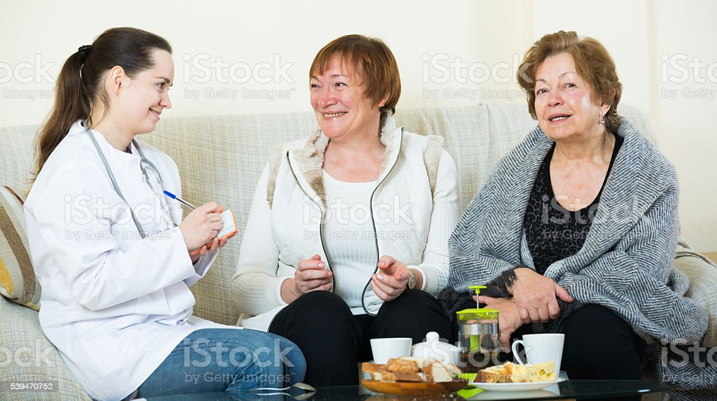 Young doctor consulting senior petients in domestic interior stock photo