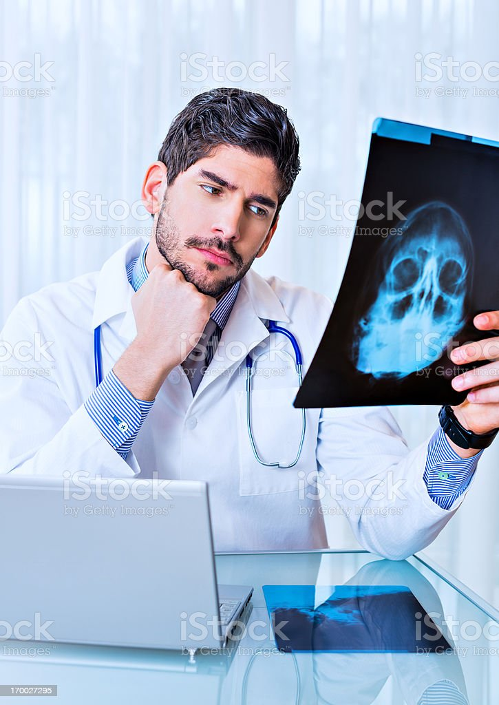 Young doctor evaluating an X-ray film royalty-free stock photo