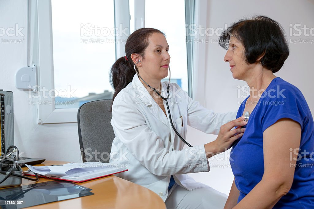 Young doctor examining her senior patient with a stethoscope stock photo