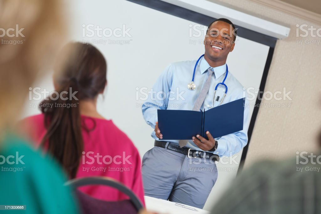 Young doctor giving presentation to nursing students in class royalty-free stock photo