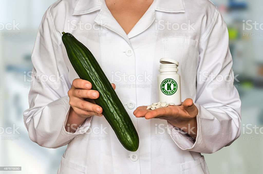 Young doctor holding cucumber and bottle of pills stock photo