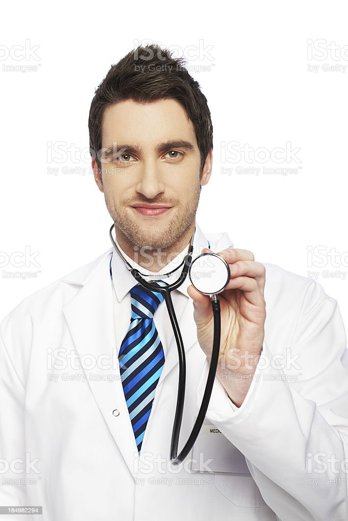 Young doctor holding his stethoscope towards camera. royalty-free stock photo