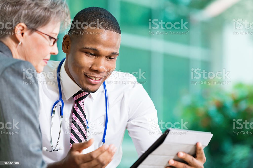 Young doctor meeting with senior adult patient in office stock photo