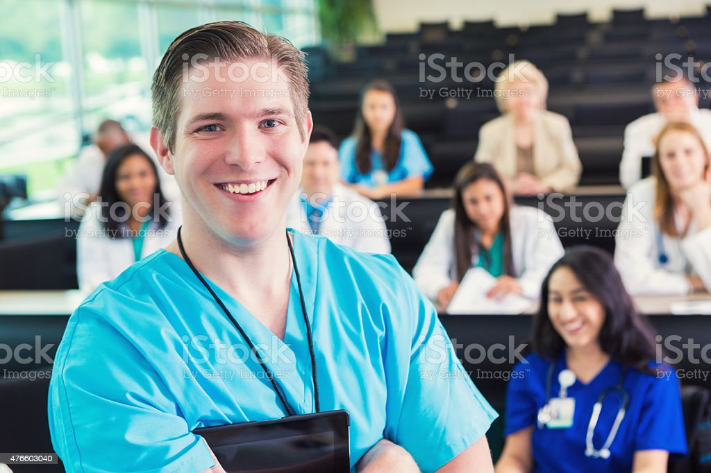 Young doctor or medical student smiling at healthcare conference stock photo