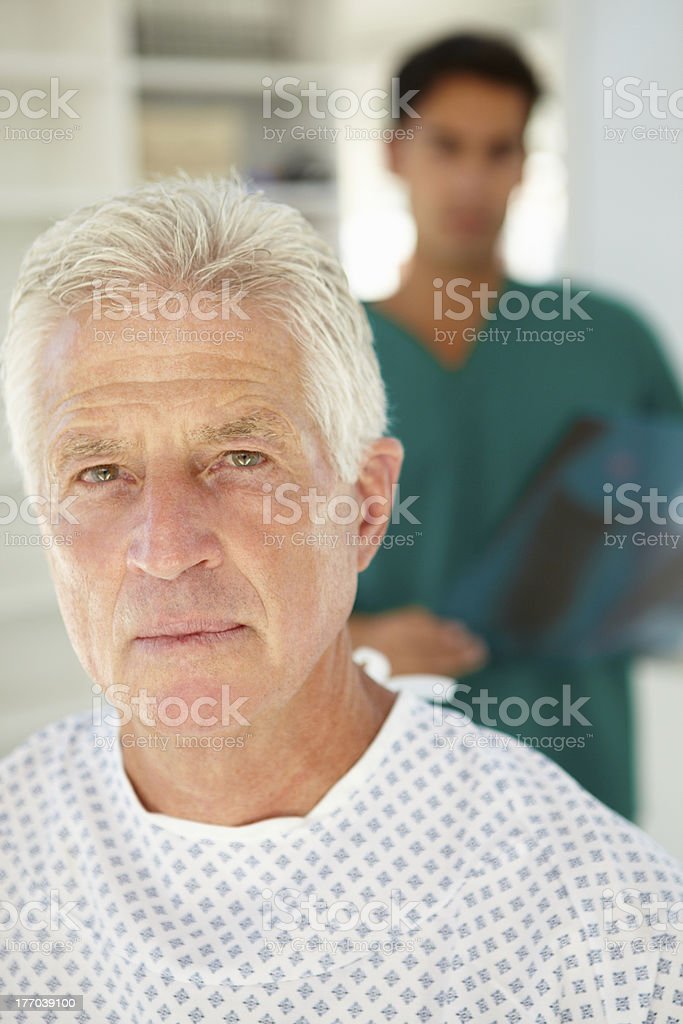 Young doctor standing behind elderly patient royalty-free stock photo