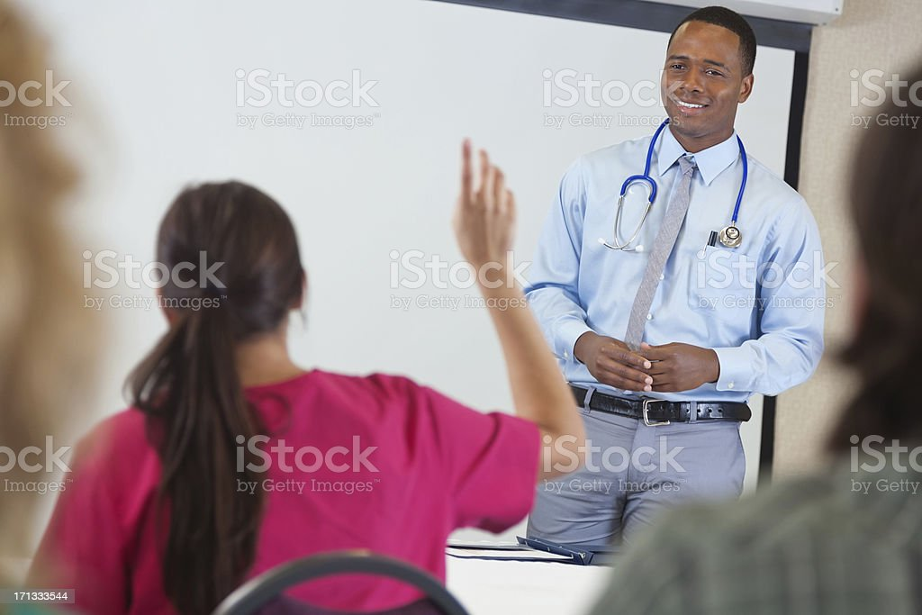 Young doctor taking questions during medical class or seminar royalty-free stock photo