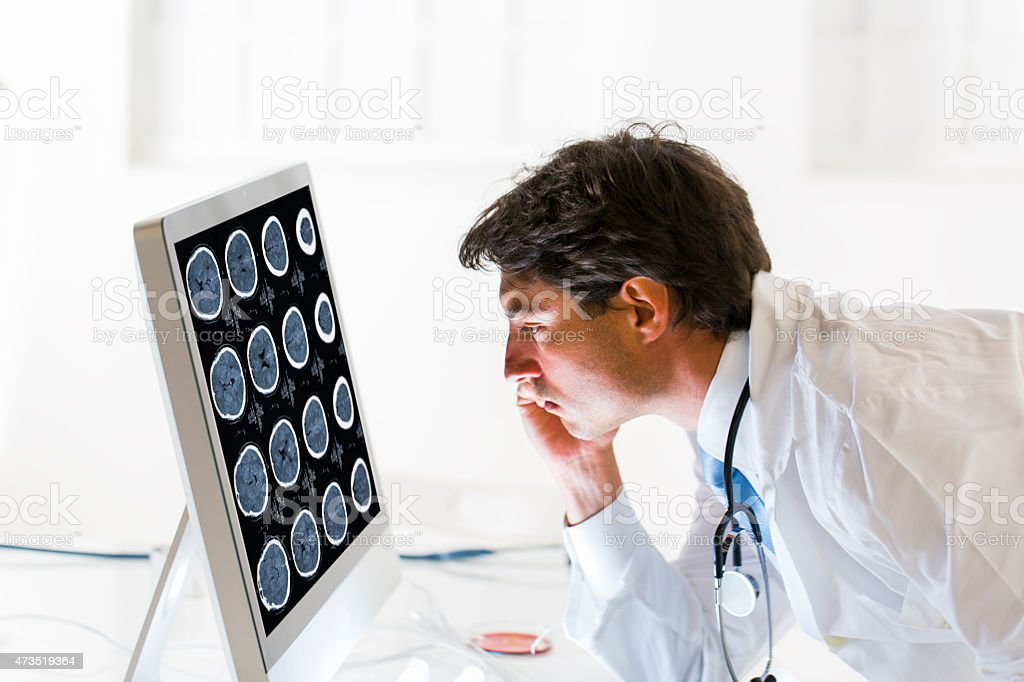 Young doctor watching CAT scan picture on monitor stock photo