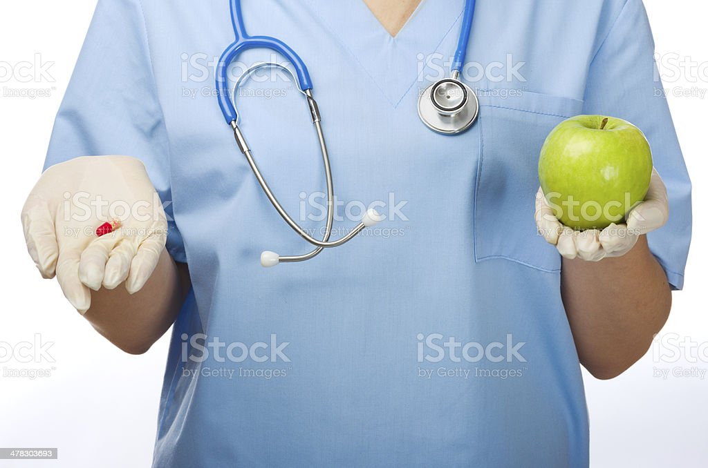 Young doctor with pill and apple royalty-free stock photo