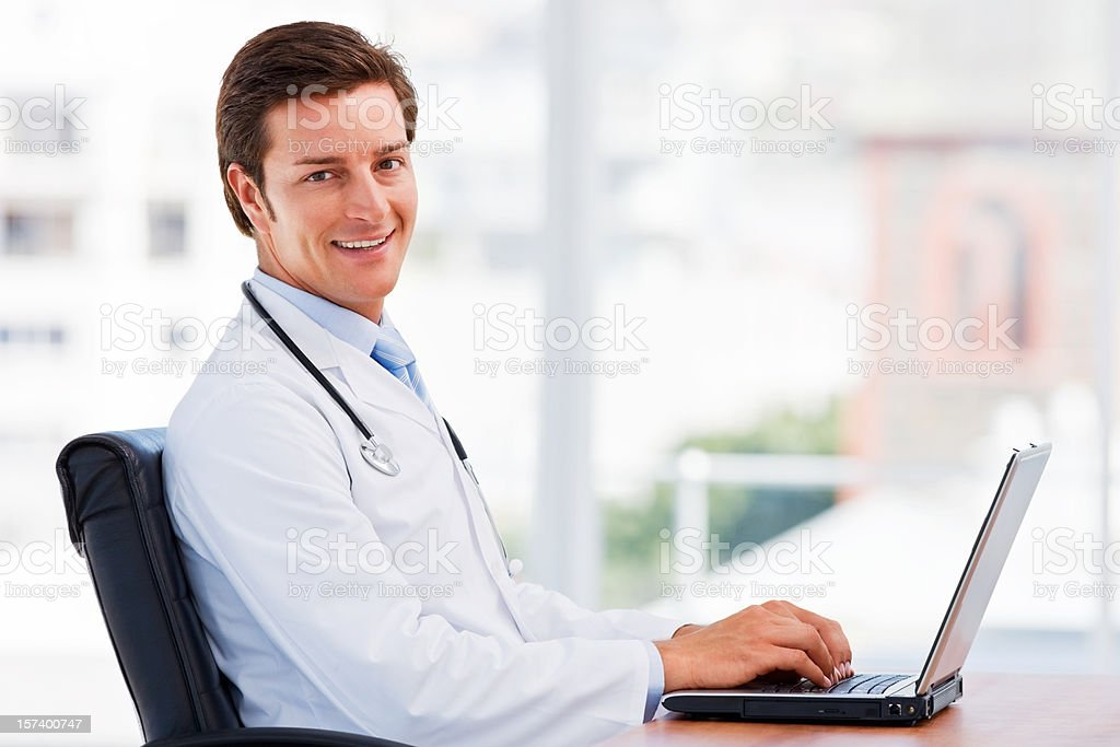Young doctor working on laptop royalty-free stock photo