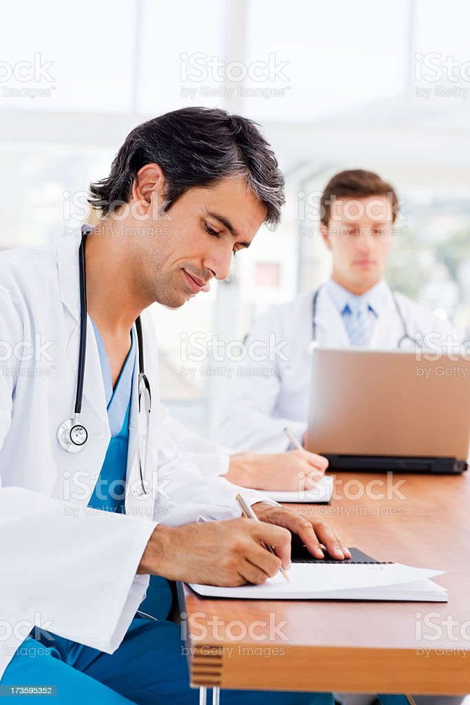 Young doctor writing reports with colleague in background royalty-free stock photo