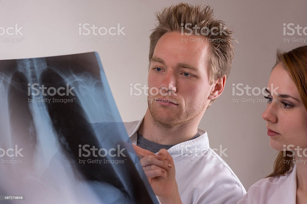 Young doctors consult over an X-ray royalty-free stock photo