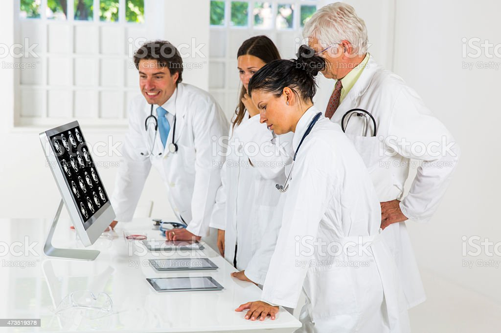 Young doctors  watching CAT scan picture on monitor stock photo