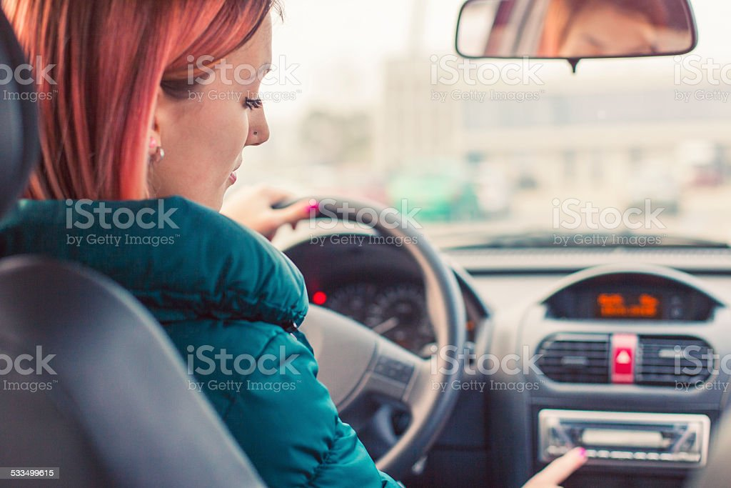 Young driver changing radio stations stock photo