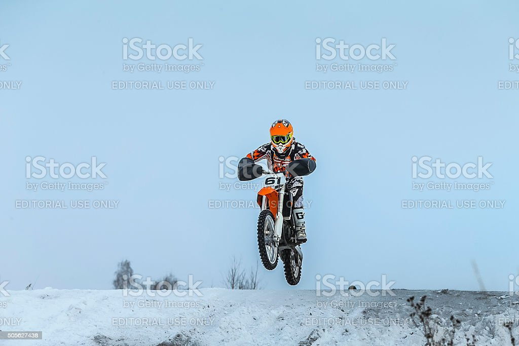 young driver on motorcycle jumps over mountain stock photo