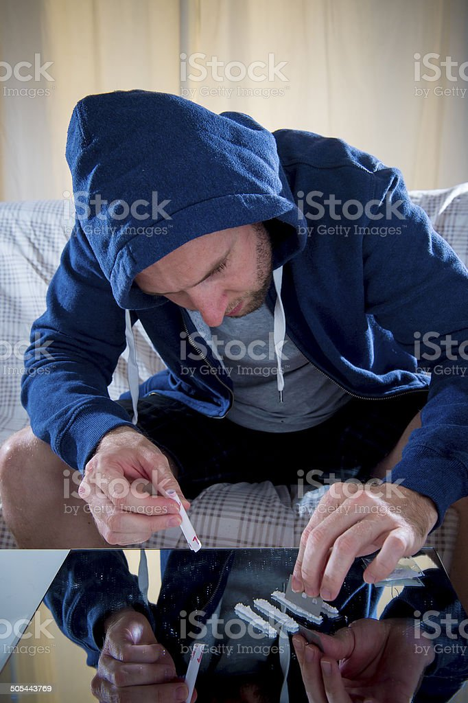 young drug addict man on hood sniffing cocaine on mirror stock photo