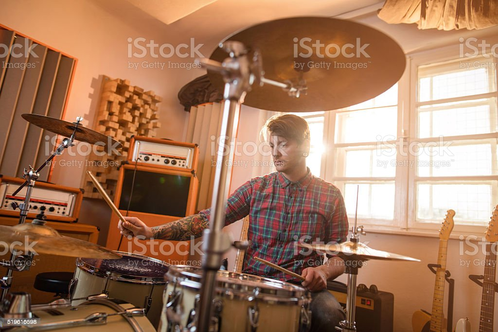 Young drummer in music studio playing drums. stock photo