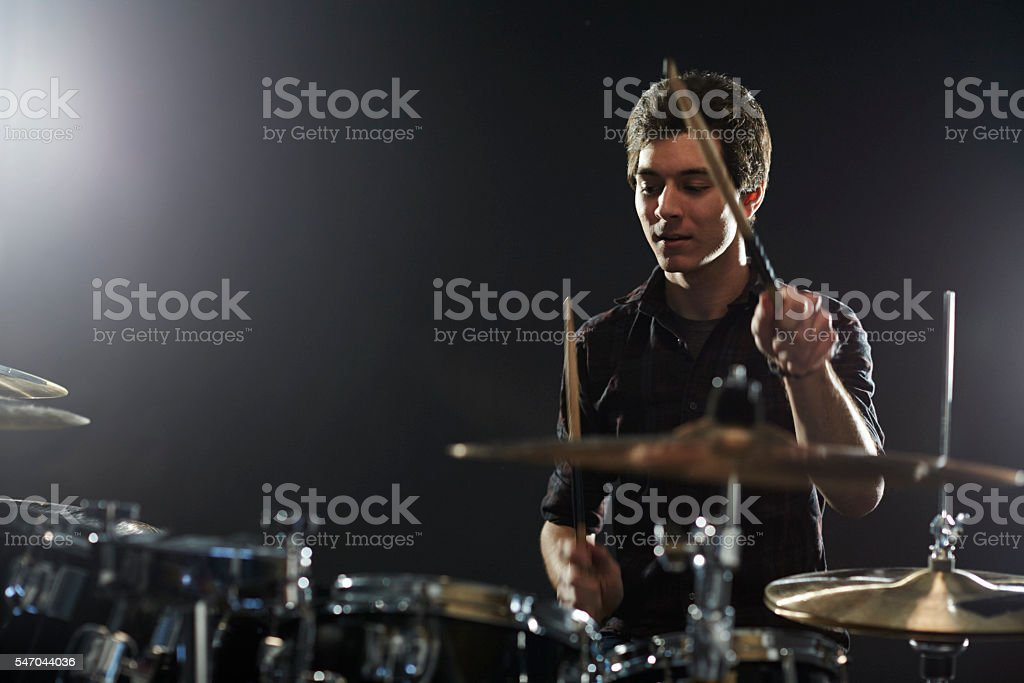 Young Drummer Playing Drum Kit In Studio stock photo