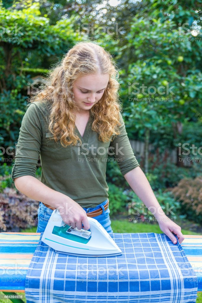 Young dutch woman ironing tea towel outdoors stock photo