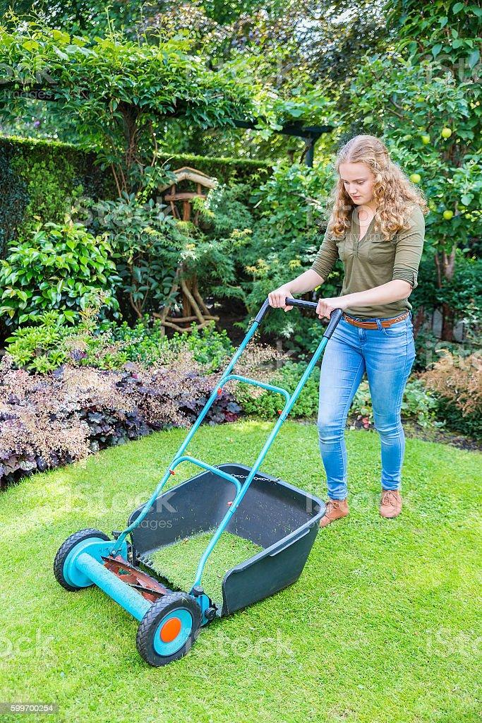 Young dutch woman pushing lawn mower on grass stock photo