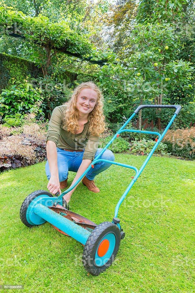 Young dutch woman reparing lawn mower in garden stock photo