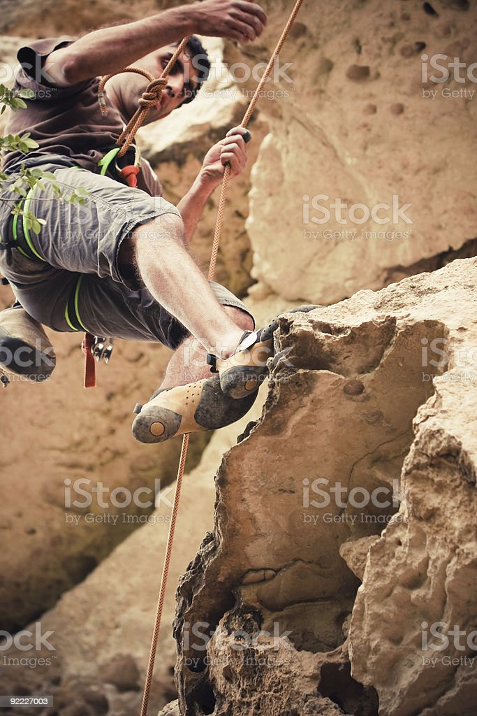 Young East Indian Asian Male climber descending rock wall royalty-free stock photo