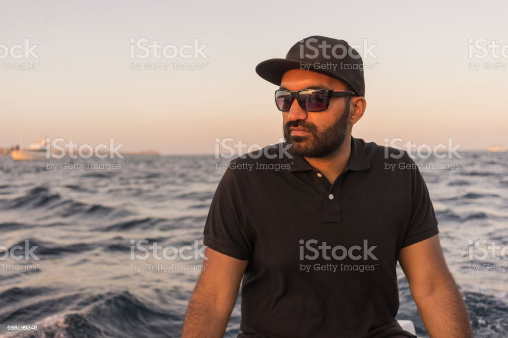 Young East Indian man fishing on open water from the boat at sunset. stock photo