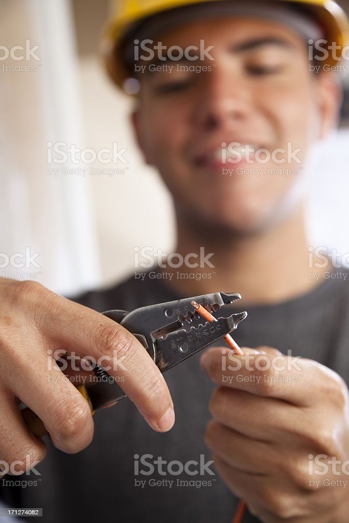 Young electrician cutting insulation from wire stock photo