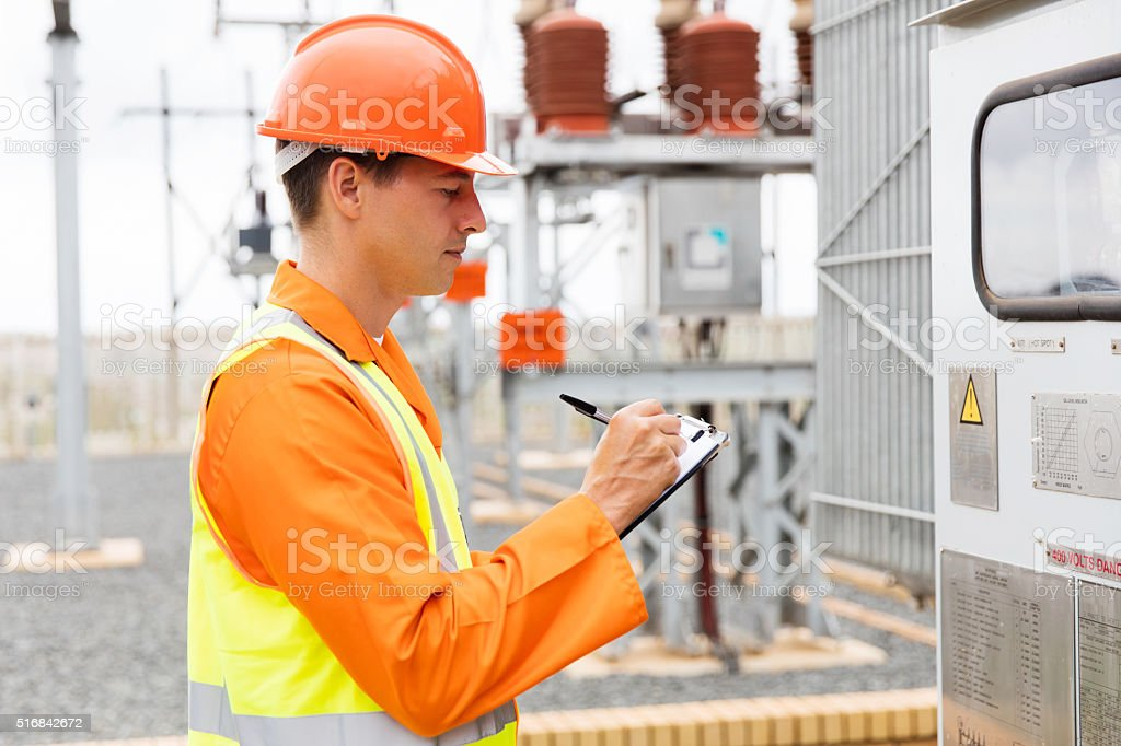 young electrician taking machine readings stock photo