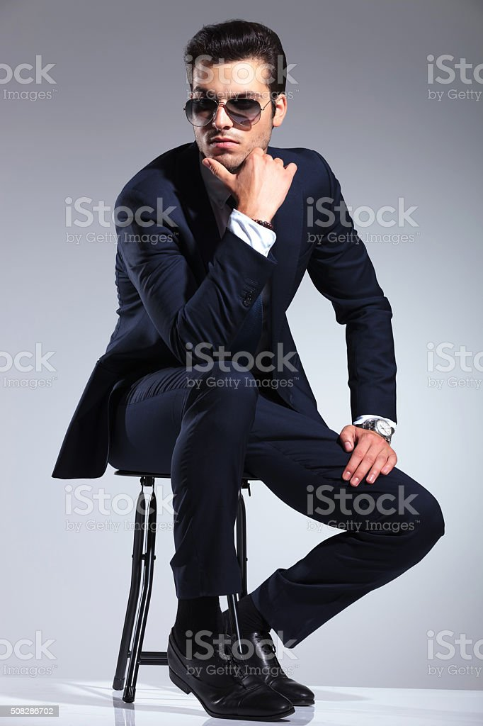 young elegant business man sitting on a stool stock photo