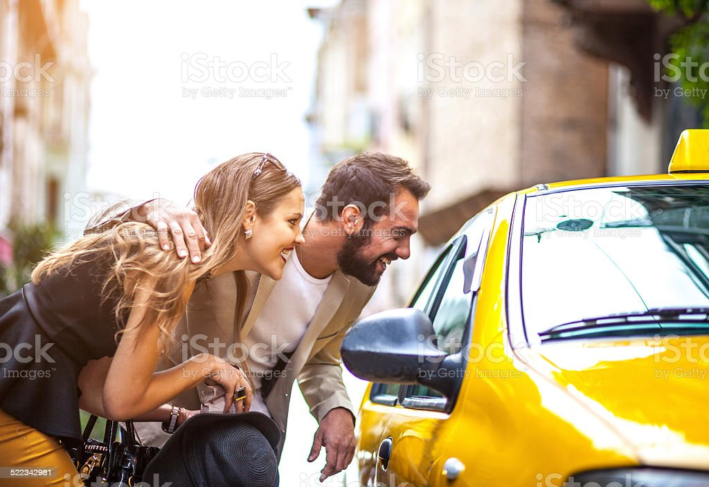 Young elegant couple taking taxi on the street stock photo