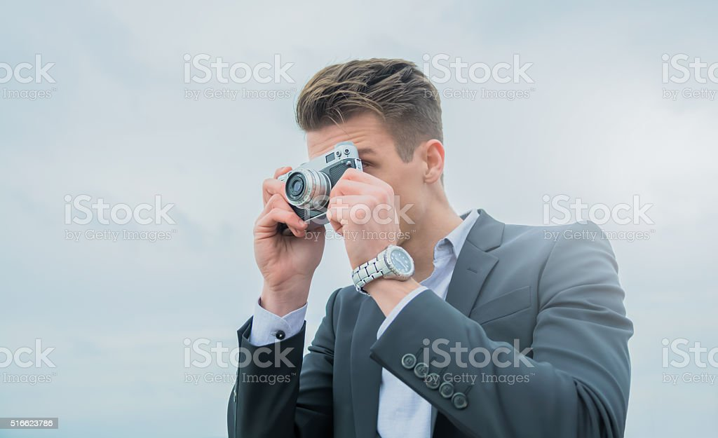 Young elegant man using an analog camera stock photo