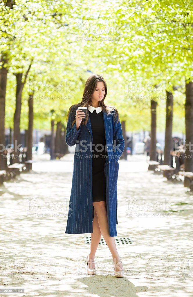 Young Elegant Woman With A Coffee Cup In A Park stock photo