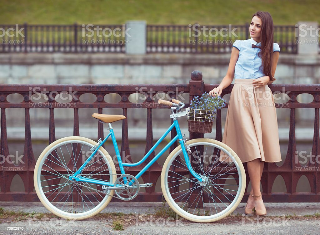 Young elegantly dressed woman with bicycle, summer and lifestyle stock photo