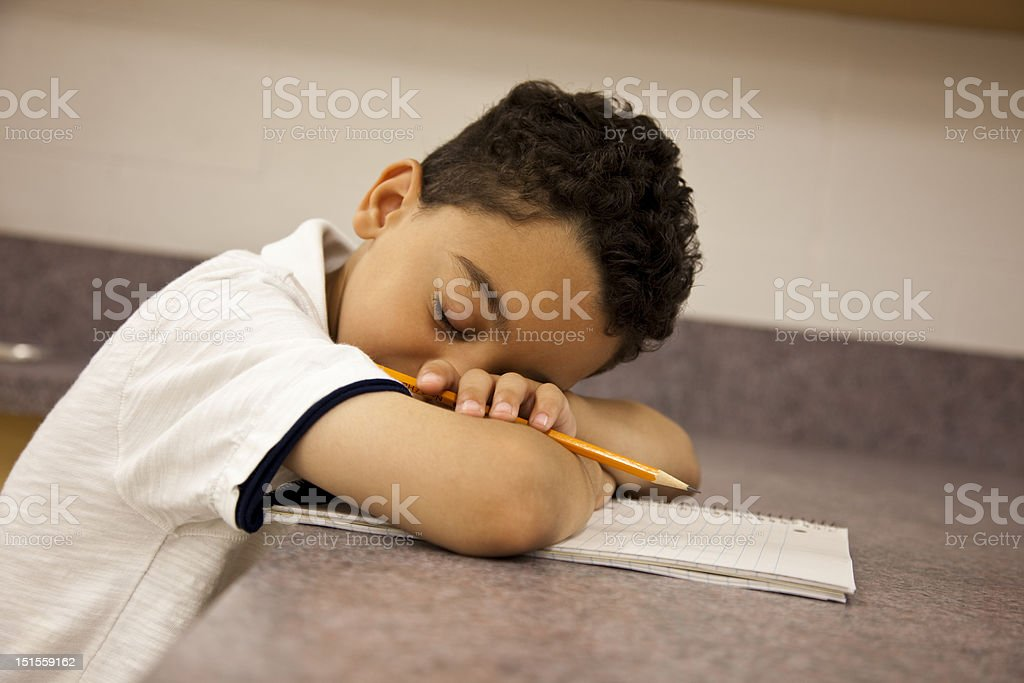 Young elementary student sleeping in class. stock photo