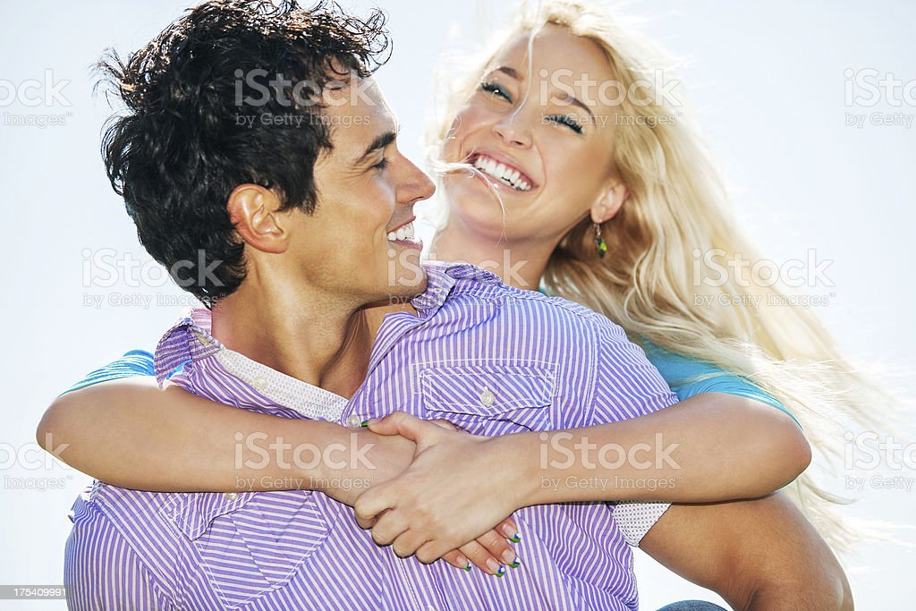 Young embraced couple against the sky. royalty-free stock photo