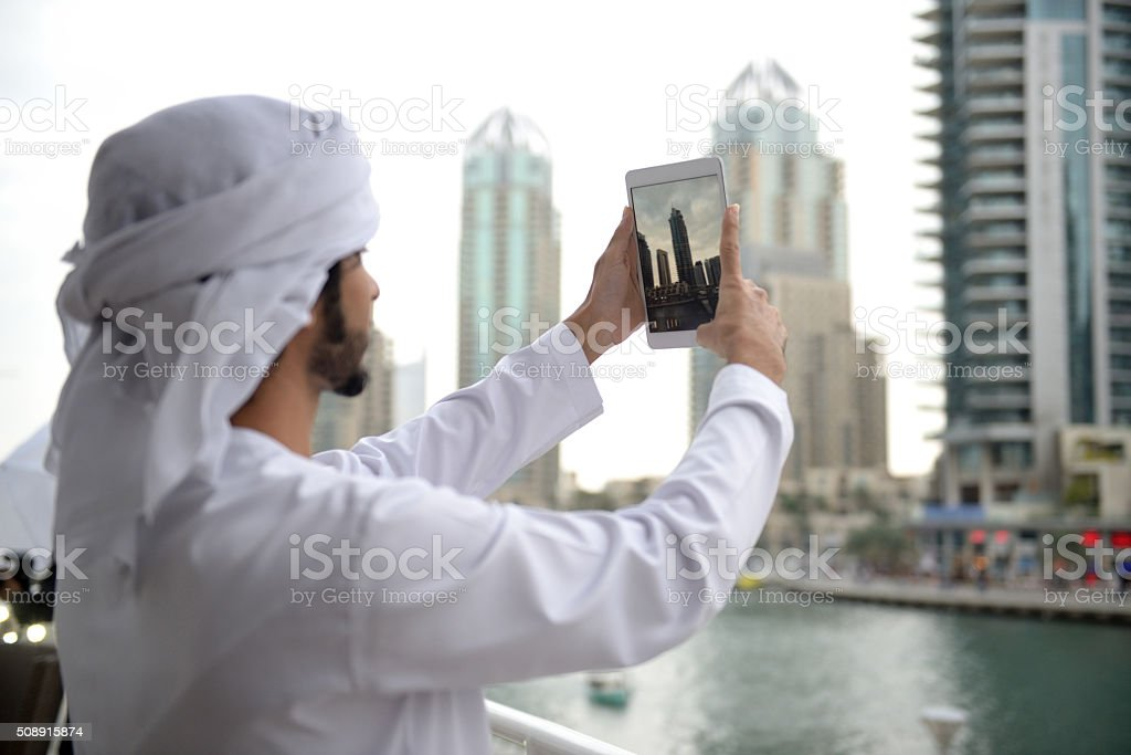 Young Emirati man taking photo with his tablet stock photo