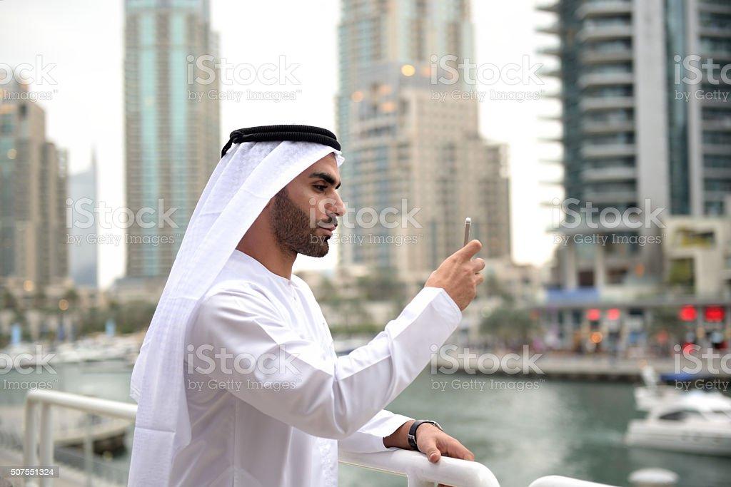 Young Emirati taking photo/selfie with smart phone stock photo