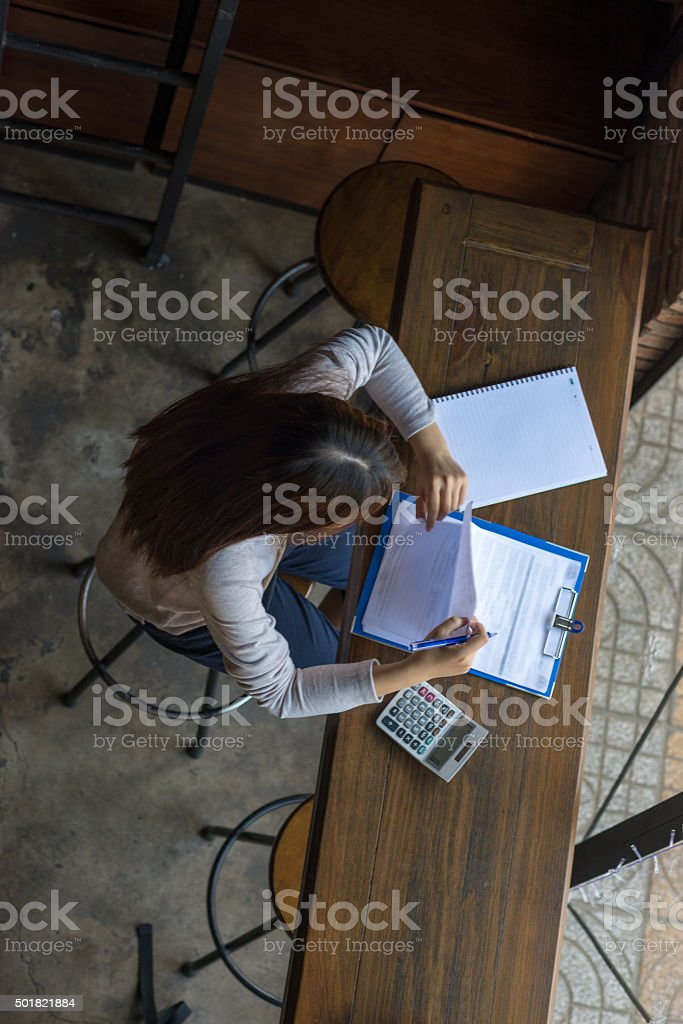 Young employee carefully checking sales reports of her company stock photo