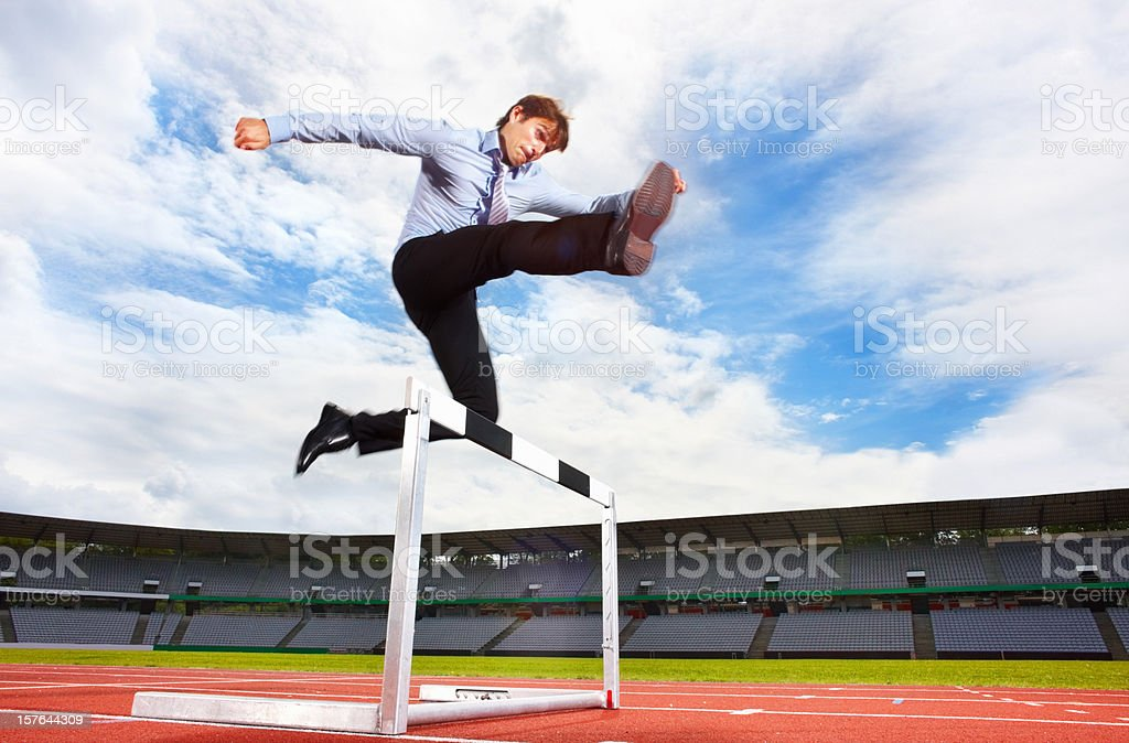 Young energetic business executive jumping over the hurdle stock photo