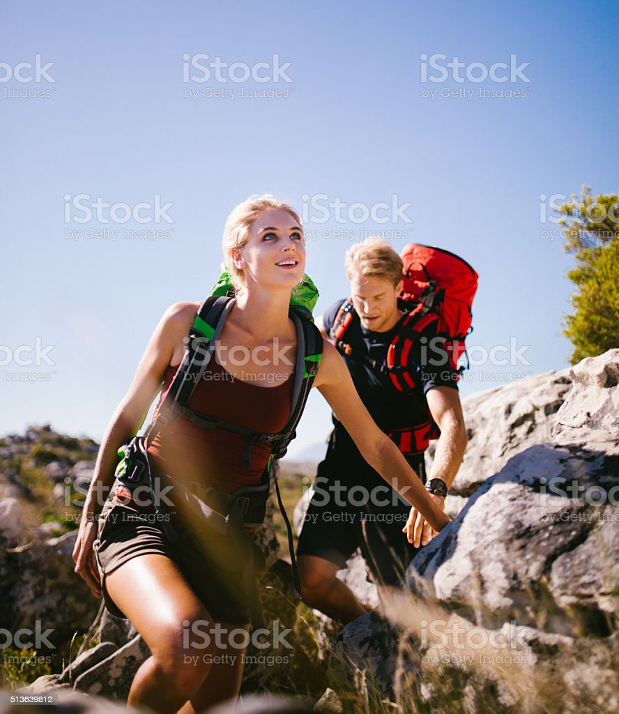 Young energetic hiker couple hiking on mountain in nature stock photo