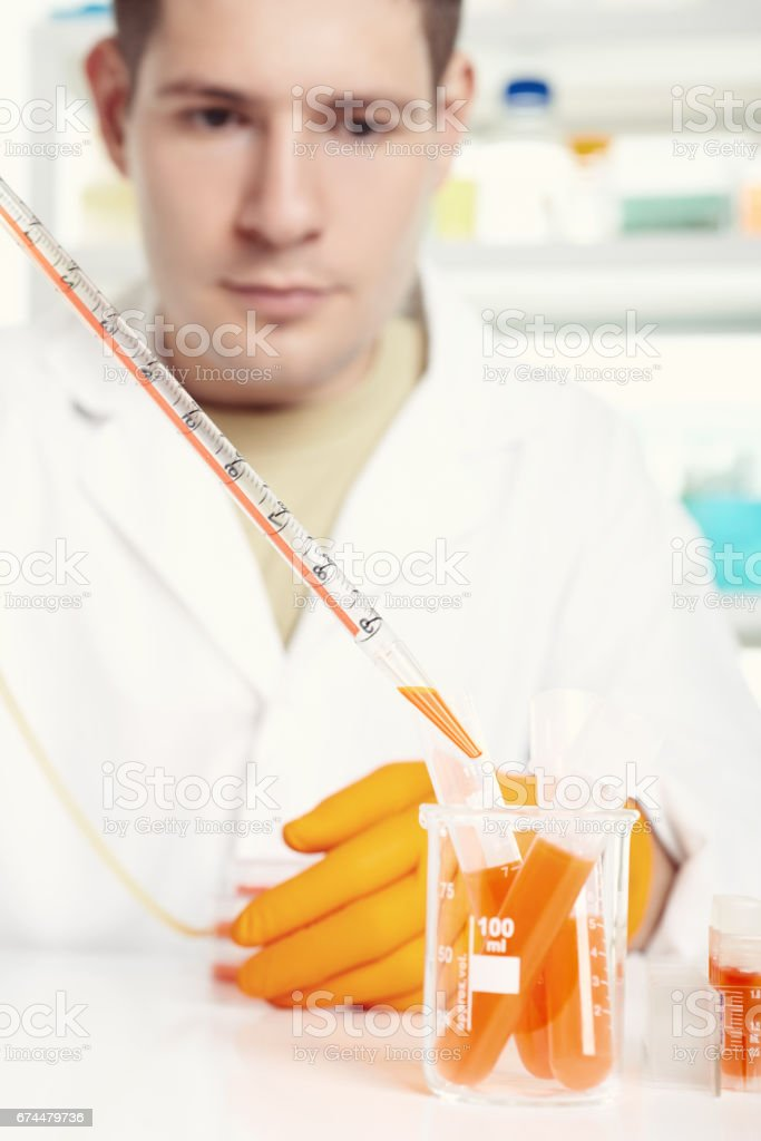 Young energetic scientist loads orange liquid sample in a tube stock photo