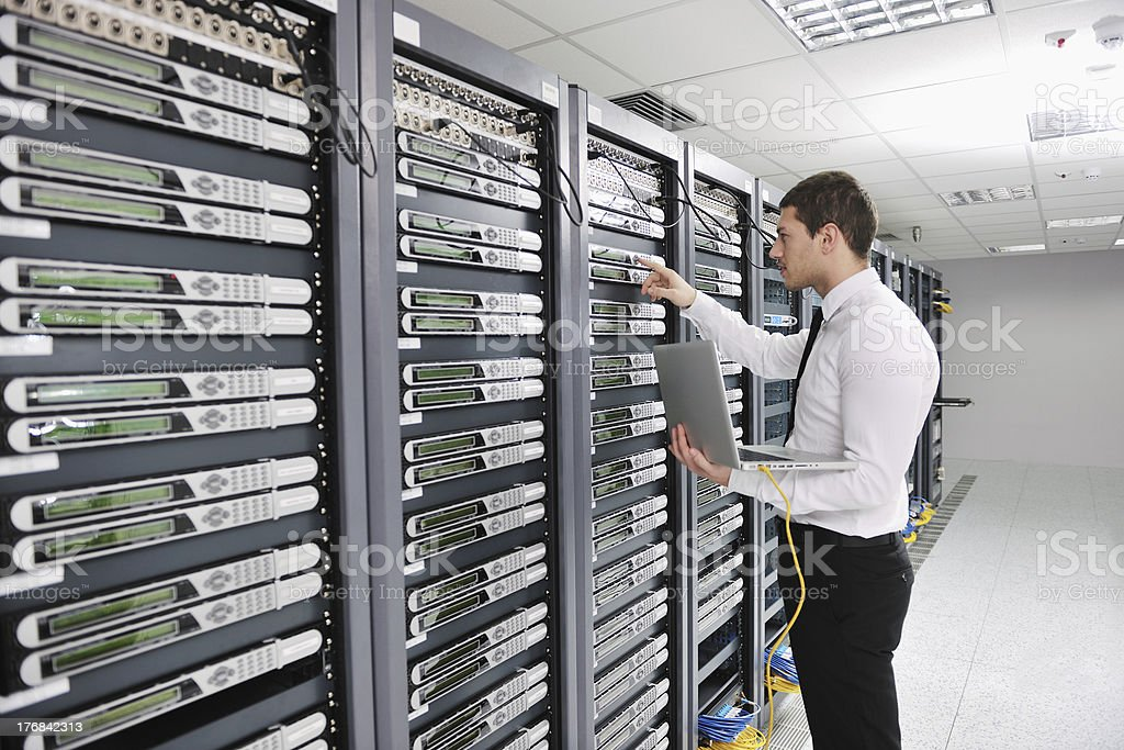 young engeneer in datacenter server room stock photo