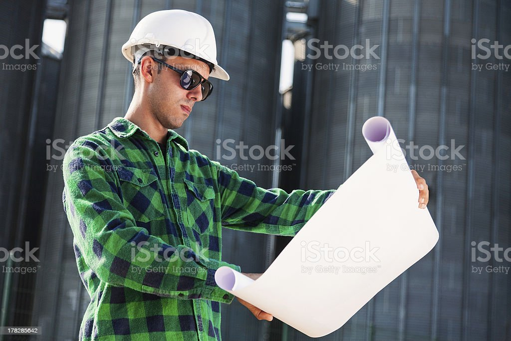 Young engineer checking blueprints royalty-free stock photo